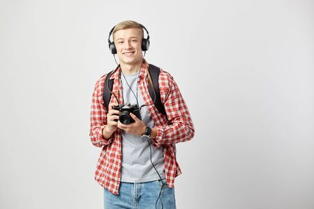Blond guy in headphones, with black backpack on his shoulder dressed in a white t-shirt, red checkered shirt and jeans holds camera in his hands on the white background Reklamní fotografie