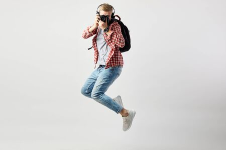 Blond guy in headphones, with black backpack on his shoulder dressed in a white t-shirt, red checkered shirt and jeans jumps and makes photos on camera on the white background in the studio