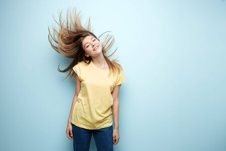 Smiling girl with flowing hair dressed in a yellow t-shirt and jeans is on a blue background in the studio