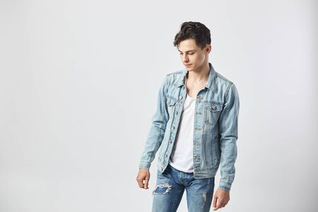 Young dark-haired guy in a white t-shirt, jeans and a denim jacket stands on the white background  in the studio