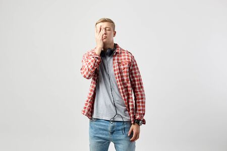 Blond guy with headphones on his neck dressed in a white t-shirt, red checkered shirt and jeans stands on the white background in the studio and holds his hand on the face