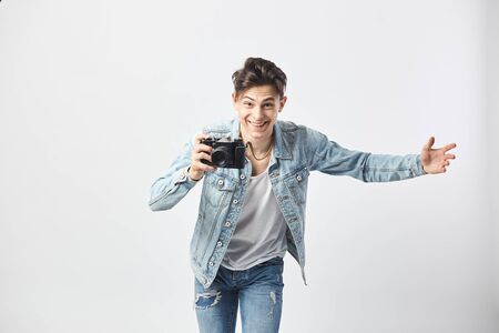 Happy dark-haired guy dressed in a white t-shirt, jeans and a denim jacket makes photos on camera on the white background in the studio