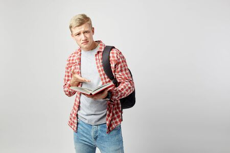 Sad blond guy with black backpack on his shoulder dressed in a white t-shirt, red checkered shirt and jeans reads a book on the white background  in the studio Reklamní fotografie
