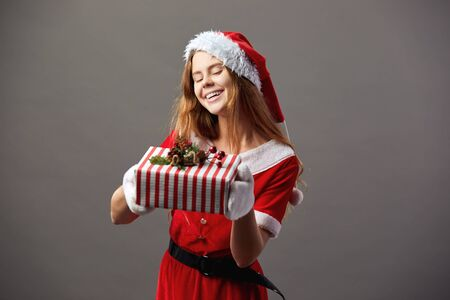 Young and beautiful mrs.Claus dressed in the red robe, Santas hat and white gloves holds the Christmas gift in her hands and smiles on the gray background.