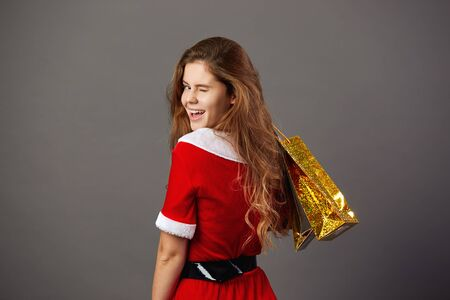 Young and beautiful woman dressed in the christmas costume holding bags with gifts and winks on the gray background