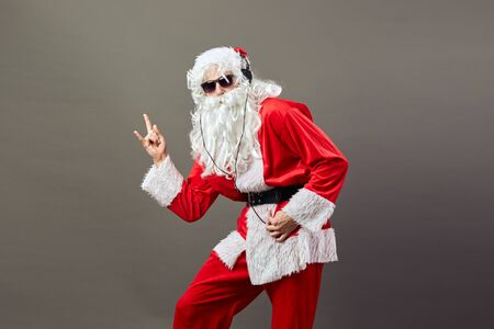 Santa Claus with a long white beard in sunglasses and headphones shows a rock sing on the gray background.