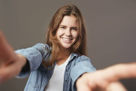 Smiling brown-haired girl dressed in a white t-shirt and jeans shirt makes a selfie on a gray background