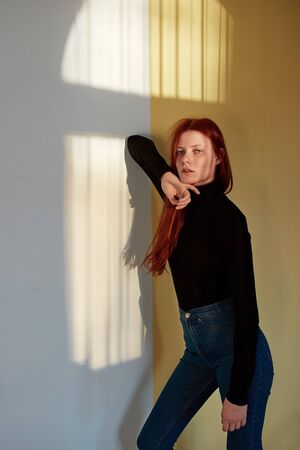 Beautiful redhead long-haired girl dressed in black top and jeans is posing against the wall with a reflection of the sunny window