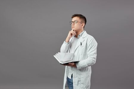 Intelligent guy in glasses dressed in a white shirt and white coat is holding a notebook and thinking on a gray background Reklamní fotografie