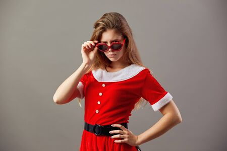 Serious charming mrs.Santa Claus in sunglasses dressed in the red robe and white gloves stands on the gray background. Reklamní fotografie