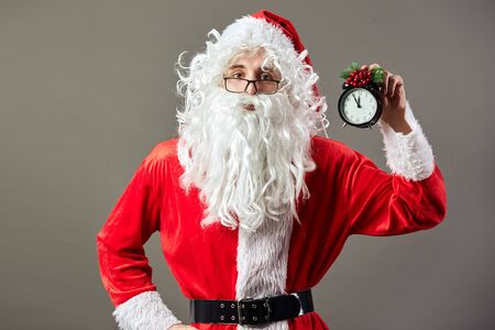 Santa Claus in glasses holds clock a clock that shows five to twelve in his hand on the gray background