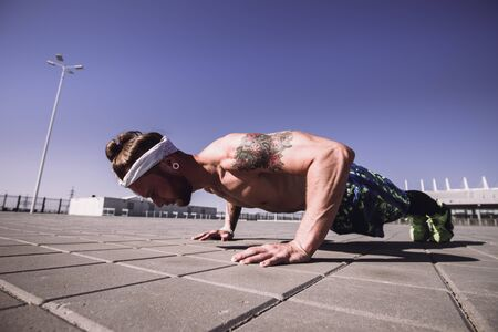 Handsome shirtless sportsman looking away doing push up exercise on workout ground outdoors at bright sunny day. Sport lifestyle