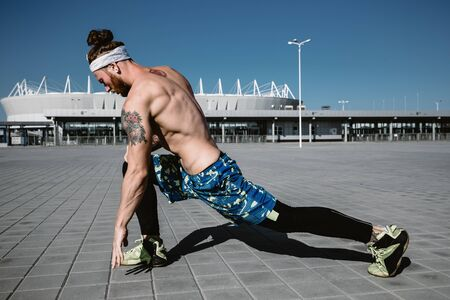 Young  athletic man with a naked torso with headband dressed in the  black leggings and blue shorts is doing stretching on paving slabs on the background of the stadium on a warm sunny day