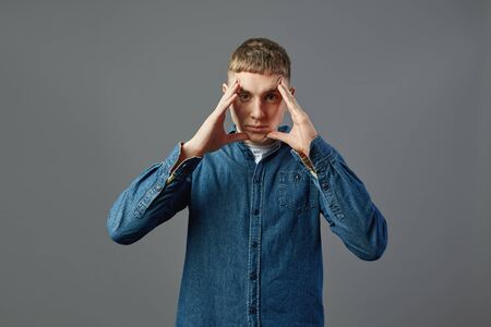 Serious guy dressed in a jeans shirt standing with his hands on his face in the studio on the gray background Reklamní fotografie