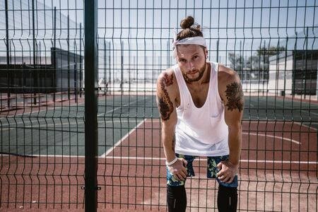 Young man with white headband  on his head and tattoos on his arms dressed in the white t-shirt, black leggings and blue shorts stands next to the playground fence outside on a sunny day