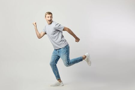 Joyful blond guy dressed in a white t-shirt and jeans happily jumping on the white background in the studio