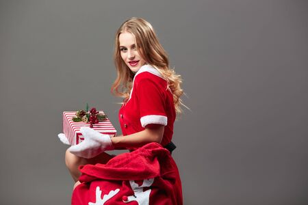 Young and beautiful mrs.Santa dressed in the red robe and white gloves sits near the bag  with Christmas gifts on the gray background.