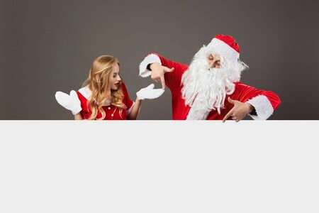 Santa Claus and young beautiful mrs. Claus stand behind a white canvas and gesticulate on the gray background. Reklamní fotografie