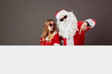 Cool Santa Claus and young beautiful mrs. Claus in sunglasses stand behind a white canvas on the gray background.