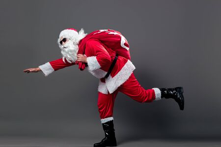 Santa Claus is running with the bag with Christmas gifts on his back on the white background.