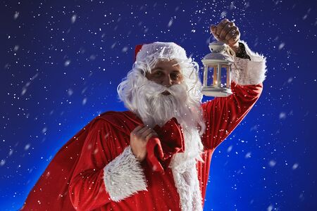 Santa Claus with a long white beard holds a lamp with a candle against a blue sky. It is snowing. Christmas