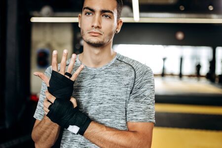 Dark-haired guy dressed in the grey t-shirt and black shorts stands  in the gym next the boxing ring and wraps a hand bandage on his hand