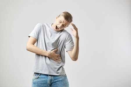 Blond guy dressed in a white t-shirt and jeans feels pain and holds hands on his stomach  on the white background in the studio