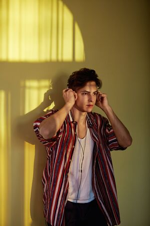 Dark-haired guy in a multi-colored striped shirt is leaning on the wall with a reflection of the sunny window