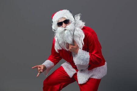 Santa Claus  with a long white beard in sunglasses and headphones stands shows a rock sing on the white background.