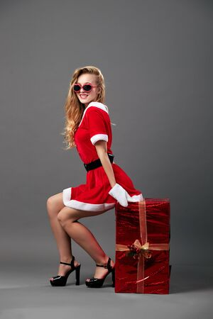 Young and beautiful mrs.Santa Claus in sunglasses dressed in the red robe, white gloves and high heels sits on the huge  Christmas present on the gray background.