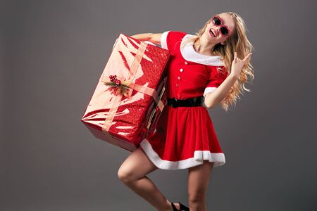 Young and beautiful mrs.Santa Claus in sunglasses dressed in the red robe, white gloves and high heels holds the huge  Christmas present on the gray background. Reklamní fotografie