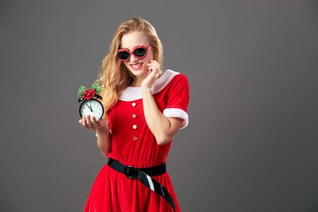 Young and beautiful mrs.Santa Claus in sunglasses dressed in the red robe and white gloves is holding a clock that shows five to twelve. Christmas Eve