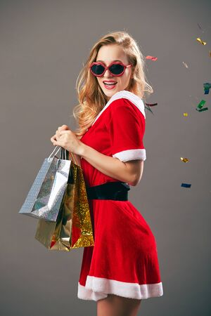 Young and beautiful mrs.Santa Claus in sunglasses dressed in the red robe and white gloves holds the bags with gifts and smiles on the gray background with confetti. Reklamní fotografie
