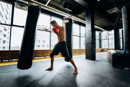 Guy in red boxing gloves with a naked torso dressed in the black shorts hits punching bag  in the gym  against the background of panoramic windows Reklamní fotografie