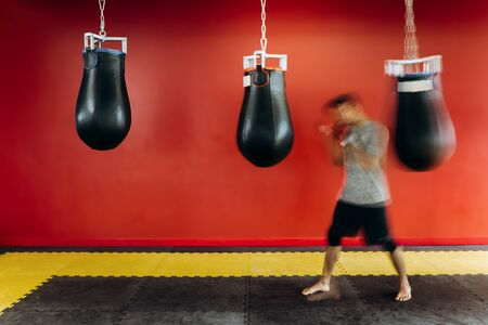 Guy dressed in the grey t-shirt and black shorts works out with a black punching bag against a red wall in the gym
