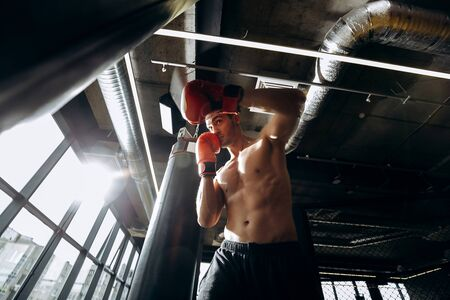 Sportsman in red boxing gloves with a naked torso dressed in the black shorts hits punching bag in the gym  with panoramic windows
