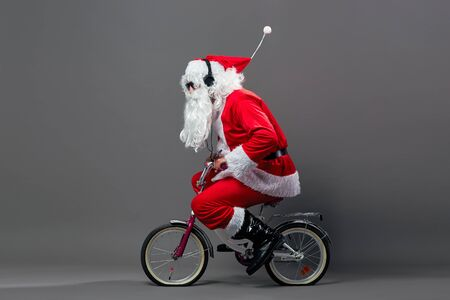 Funny Santa Claus with a long white beard in sunglasses and headphones rides a bicycle on the white background. Stock Photo