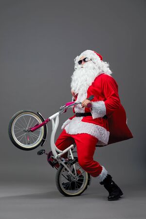 Santa Claus in sunglasses and headphones puts the bike on the back wheel on the white background.