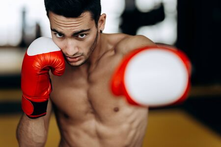 Sportsman with a naked torso and the red boxing gloves  his hands stands hits with left hand in the boxing gym