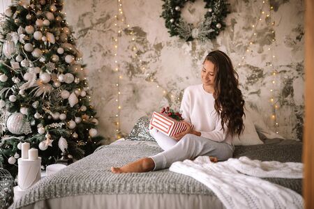 Dark-haired girl dressed in white sweater and pants holds a New Year gift in her hands sitting on the bed with gray blanket and white pillows in a decorated room with a New Year tree and candles Reklamní fotografie