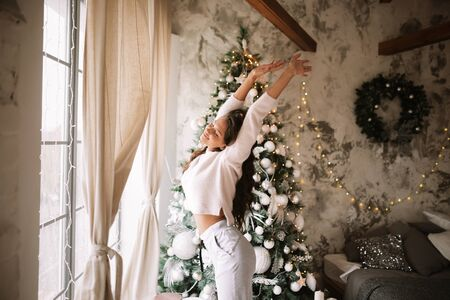 Charming girl dressed in white sweater and pants stands next to the New Year tree in front of the window and stretches up  in a cozy decorated room  with New Years wreath Reklamní fotografie