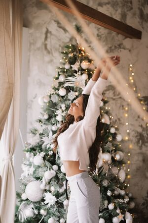 Charming girl dressed in white sweater and pants stands next to the New Year tree in front of the window and stretches up  in a cozy decorated room Reklamní fotografie
