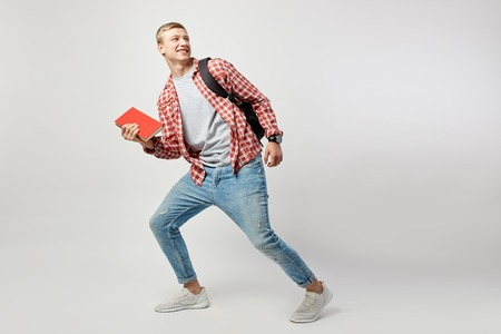 Joyful blond guy with black backpack on his shoulder dressed in a white t-shirt, red checkered shirt and jeans holds book in his hand and shouts on the white background in the studio