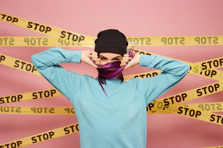 Girl with purple hair tips dressed in blue sweatshirt and black hat is grimacing on the background of pink wall with the yellow scotch tapes with inscriptions of word