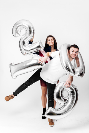 Girl and guy dressed in a stylish smart clothes are having fun with balloons in the shape of numbers 2019 on a white background in the studio