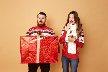 The girl holding a little gift surprisely looks at the guy holding a huge gift. They both are dressed in red and white sweaters with deer Stock Photo