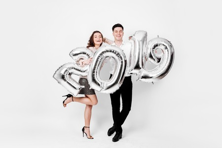 Happy girl and guy dressed in a stylish smart clothes are holding balloons in the shape of numbers 2019 on a white background in the studio