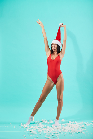 Shapely dark-haired girl in Santa Claus hat dressed in red swimsuit stands on the floor with snow and holds up the top of the hat on the blue background in the studio
