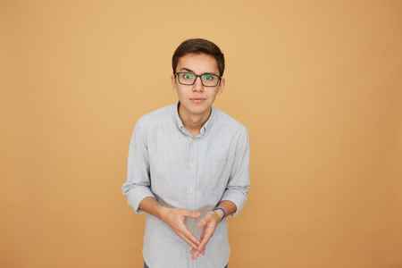 Young guy in glasses dressed in light blue shirt stands with his eyes wide open on the beige background in the studio