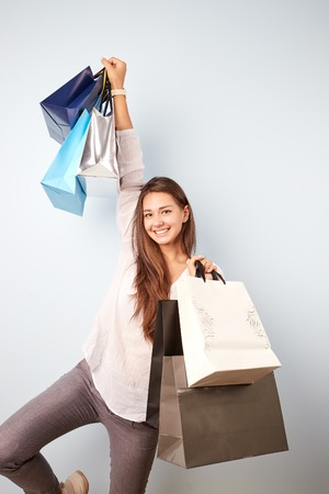 Joyful brown-haired girl dressed  in white blouse and gray trousers holds lots of bags after shopping on the white background
